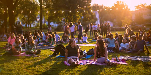 Photo of students on a campus lawn during an outdoors vespers.