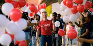 Photo of a freshman surrounded by balloons.